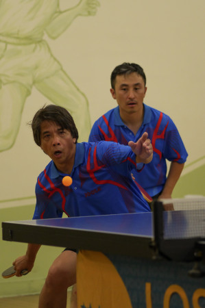 Gerry Chua sets up to rip a forehand loop as doubles teammate June Lim watches in anticipation
