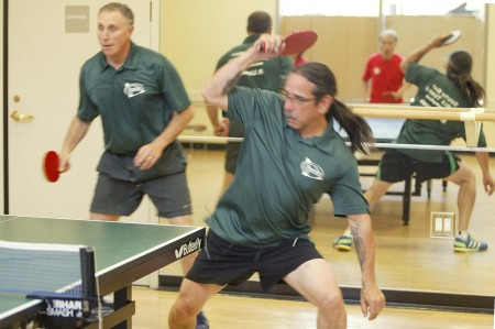 South Bay Eagle Paul Limburg waits in the back while his doubles partner Steve Sakurada loops aggressively against the Golden Ninjas seen reflected in the mirror.